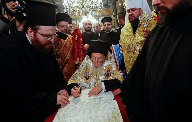 Вселенский патриарх Варфоломей подписывает Томос. Фото: president.gov.ua